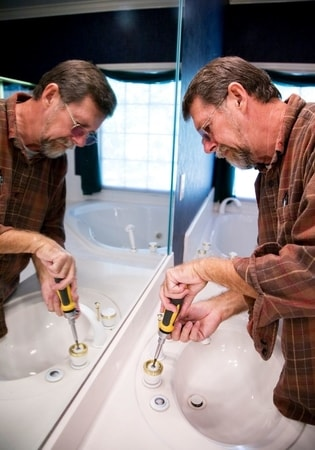 old man using screwdriver to fix sink at townsville handyman